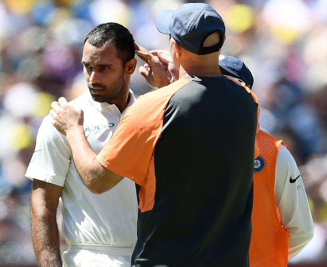 Physio Patrick Farhat checks on Hanuma Vihari after he was hit on the helmet by a bouncer from Pat Cummins. Photograph: Michael Dodge/Getty Images