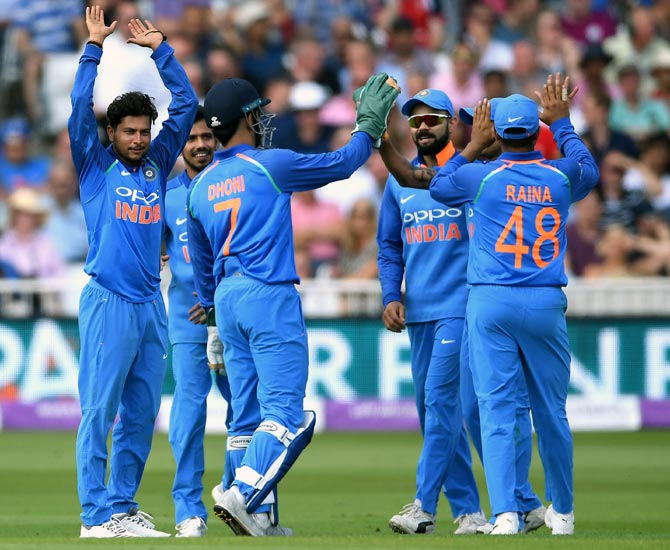 Kuldeep Yadav, left, celebrates with team mates after taking the wicket of Ben Stokes