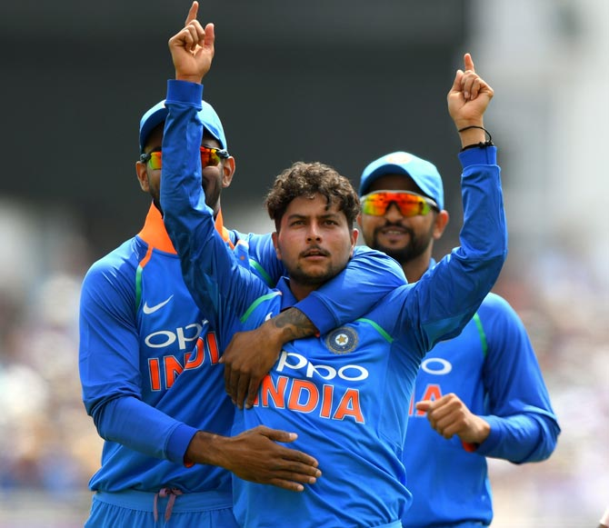 Kuldeep Yadav is congratulated by skipper Virat Kohli and Suresh Raina after dismissing England's Joe Root