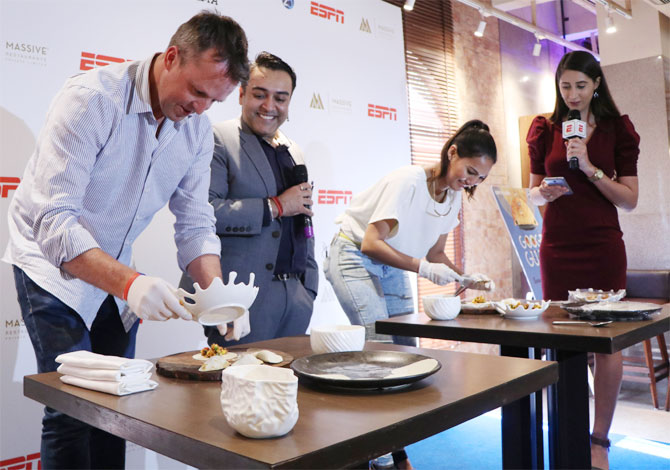 Former England off-spinner Greame Swann and television presenter Rochelle Rao prepare 'Google Gujiya' as Massive Restaurants' Zorawar Kalra (centre) eggs them on
