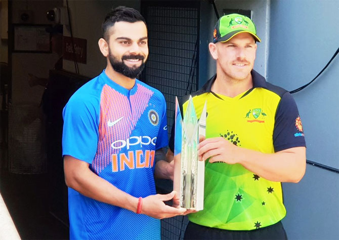 India captain Virat Kohli and Australia captain Aaron Finch pose with the T20 Trophy on the eve of the first T20 in Brisbane on Tuesday