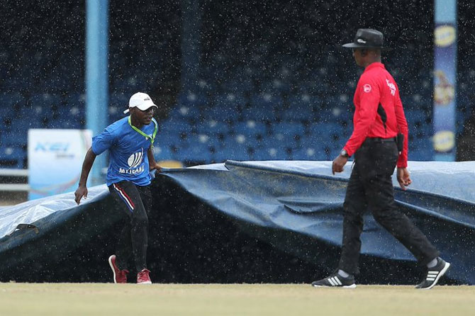 A groundsman runs in with the covers as rain interrupts play during the India innings
