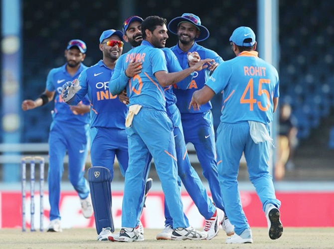 India pacer Bhuvneshwar Kumar is congratulated by skipper Virat Kohli and teammates after dismissing Roston Chase