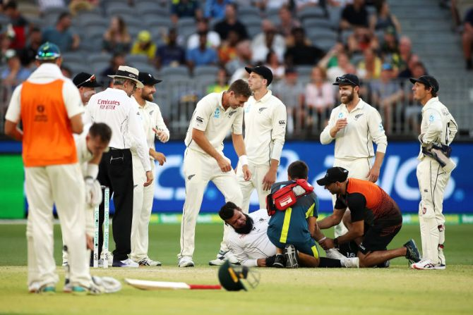 Umpire Aleem Dar receives attention after he collided with New Zealand's Mitchell Santner