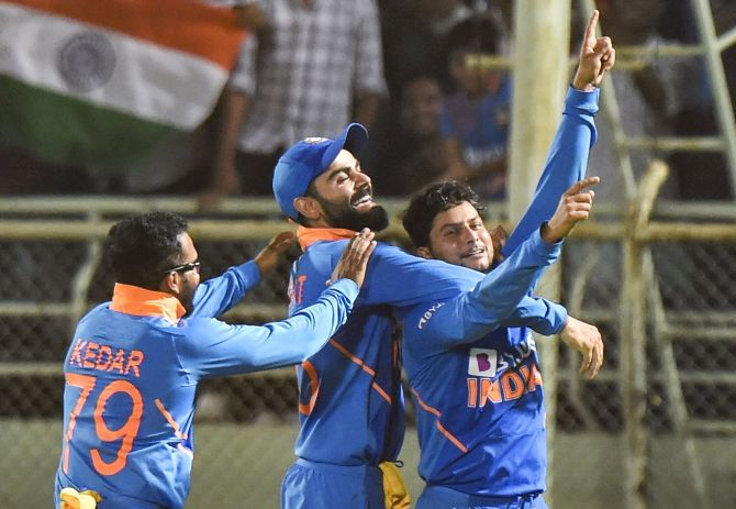 India's Kuldeep Yadav celebrates with skipper Virat Kohli and teammate Kedar Jadhav after completing his hat-trick during the 2nd ODI cricket against West Indies at ACA-VDCA Cricket Stadium in Visakhapatnam on Wednesday