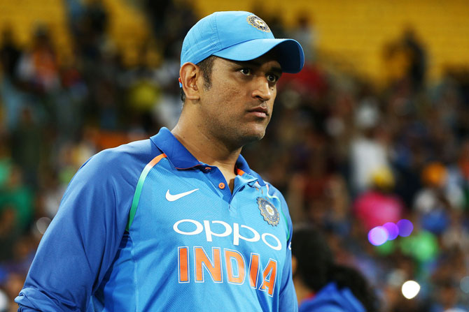 Dhoni's delirious fan, who was holding the tri-colour, breached the security and rushed towards the former Indian captain to touch his feet