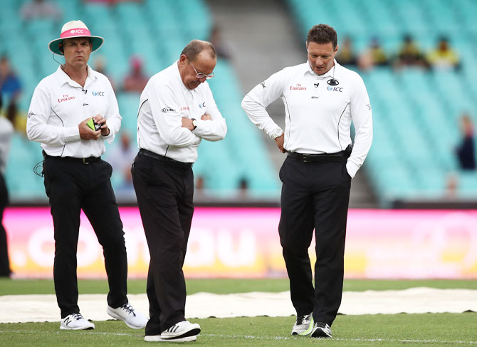 Umpires Ian Gould and Richard Kettleborough inspect conditions on the field