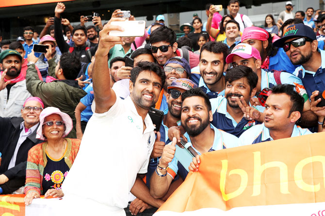 Ravichandran Ashwin celebrates with members of the Bharat Army after India's 2-1 series win on Monday