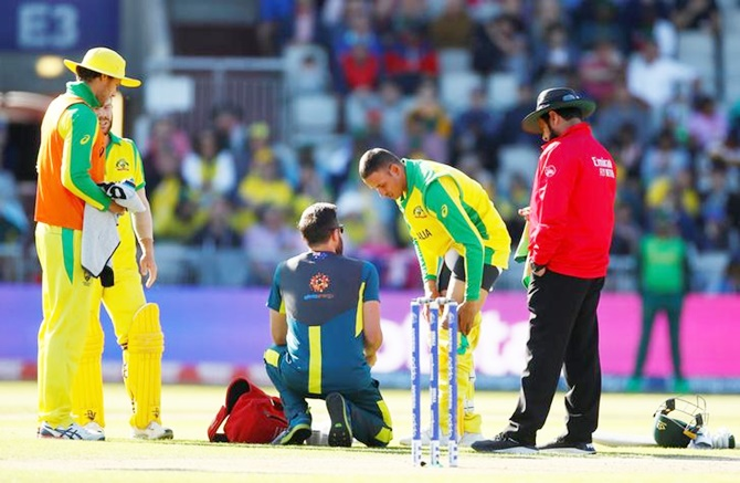 Usman Khawaja gets treatment after suffering a hamstring injury while batting during Saturday's World Cup match against South Africa