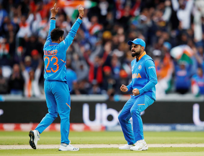 India's Kuldeep Yadav celebrates with captain Virat Kohli after picking the wicket of Pakistan's Babar Azam