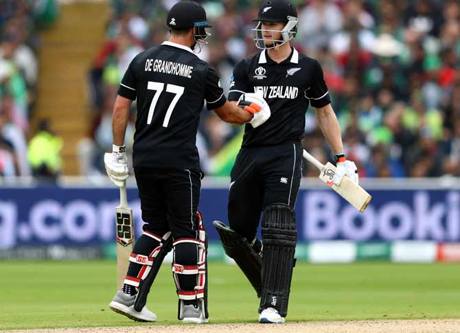 Jimmy Neesham (r) of New Zealand shakes hands with Colin de Grandhomme after reaching his fifty
