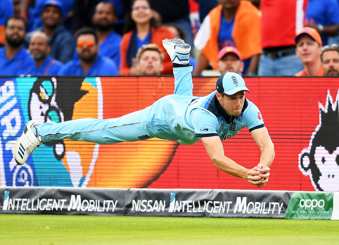 England's Chris Woakes dives to take a catch to dismiss India's Rishabh Pant during their group stage match at Edgbaston in Birmingham on June 30