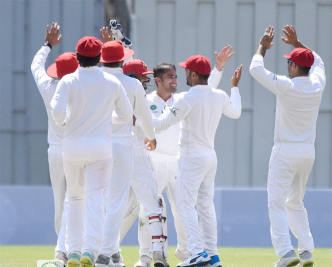 Afghanistan's Rashid Khan celebrates with teammates a the fall of an Ireland wicket in the one-off Test in Dehradun in March.