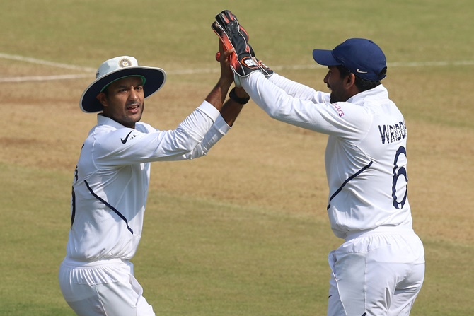 Mayank Agarwal and wicketkeeper Wriddhiman Saha celebrate the dismissal of Mohammad Mithun.