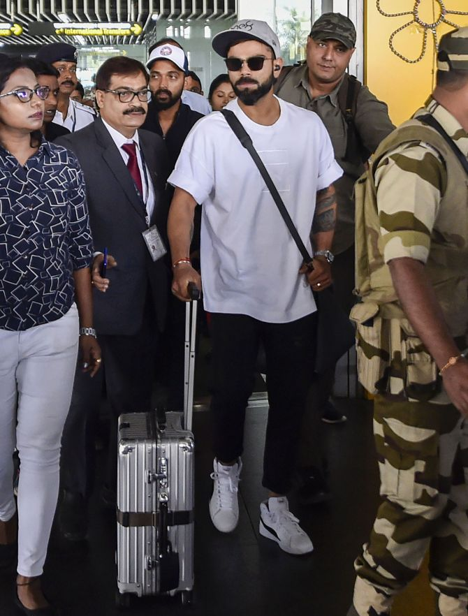 India captain Virat Kohli and Ajinjya Rahane (background) arrive at the Netaji Subhash Chandra Bose International Airport in Kolkata on Tuesday, ahead of India's first-ever Day/Night Test against Bangladesh
