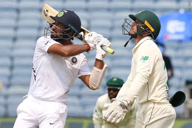 South Africa wicketkeeper Quinton de Kock watches as Cheteshwar Pujara hits a six off Senuran Muthusamy, the first of the match.