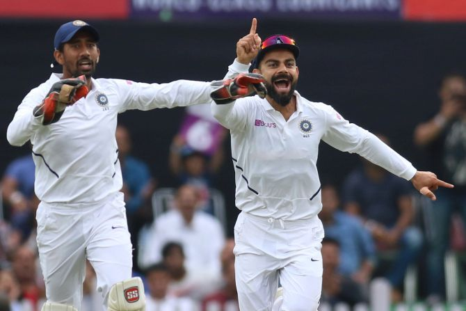 Virat Kohli and Wriddhiman Saha celebrate the wicket of South Africa's Dean Elgar