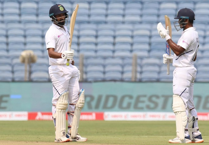 Cheteshwar Pujara celebrates his fifty.