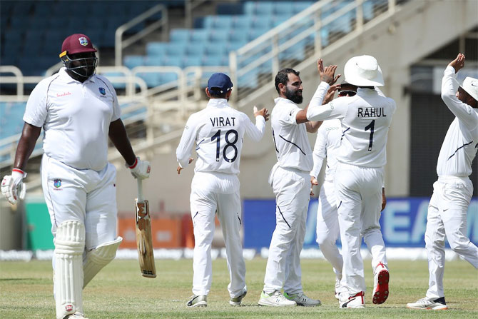 India's Mohammed Shami celebrates with teammates after taking the wicket of West Indies' Rahkeem Cornwall, his 150th Test victim