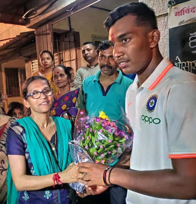 Atharva Ankolekar, right, is greeted by mother Vaidehi on his arrival in Mumbai on Sunday night.
