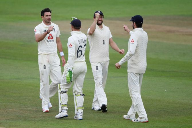 James Anderson is congratulated by Jos Buttler after taking his fifth wicket on dismissing Naseem Shah