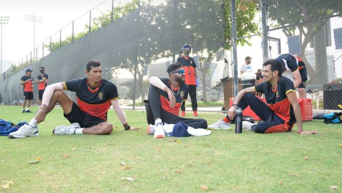 RCB's Navdeep Saini, Mohammed Siraj and Yuzvendra Chahal rest during the training session on Saturday.