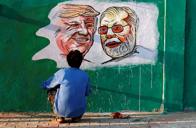 A man applies finishing touches to paintings of US President Donald Trump and India's Prime Minister Narendra Modi on a wall.