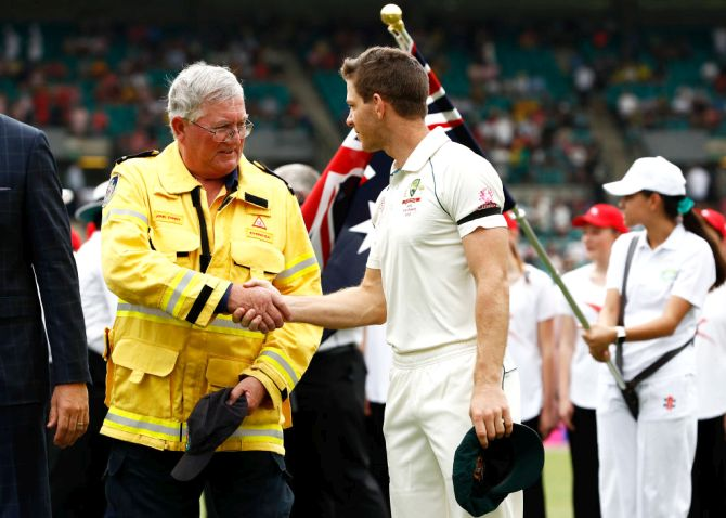 Australia captain Tim Paine speaks to Ku-ring-gai Fire Brigade Volunteer John Corry before the start of the third Test match in the series between Australia and New Zealand at Sydney Cricket Ground on Friday