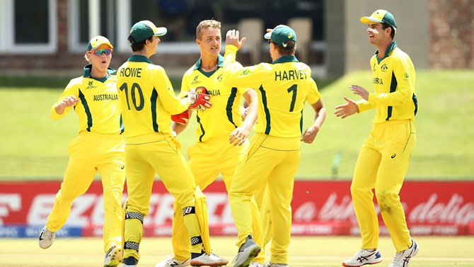 Connor Sully celebrates the fall of an India wicket with his Australia teammates.