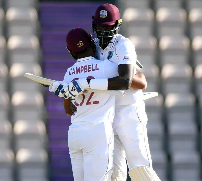 West Indies captain Jason Holder, right, celebrates with John Campbell after winning the 1st #RaiseTheBat Test match
