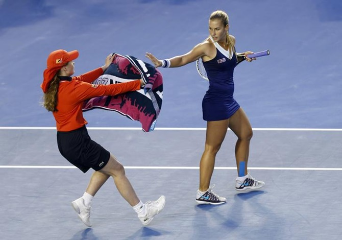 A ball kid hands Dominika Cibulkova of Slovakia a towel during her women's singles final against Li Na of China at the Australian Open 2014 tennis tournament.