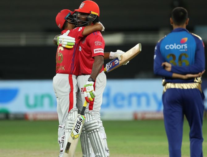 Chris Gayle and Mayank Agarwal embrace after Kings XI clinch victory over MUmbai Indians via the second Super over in Sunday's IPL match in Dubai
