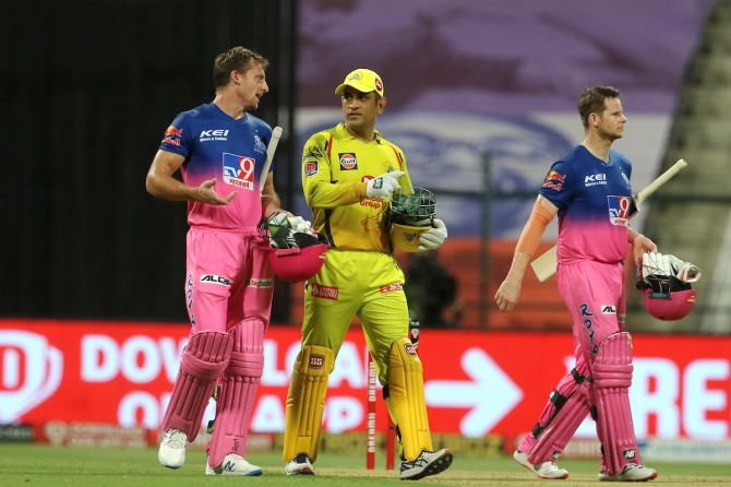 Rajasthan Royals batsmen Jos Buttler and Steven Smith walk back with Chennai Super Kings skipper Mahendra Dhoni after clinching victory in the IPL match in Abu Dhabi on Monday.