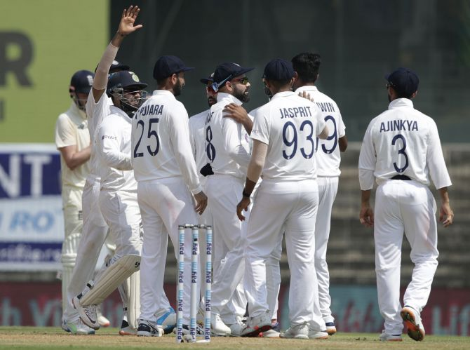 India's players celebrate the wicket of Rory Burns.