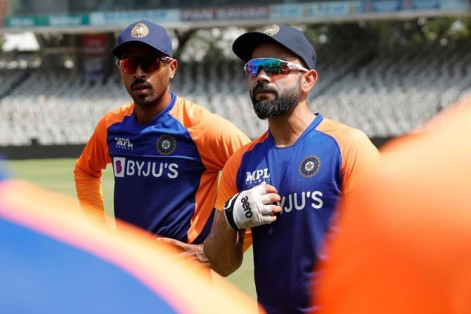 Virat Kohli speaks to players in the nets on Friday