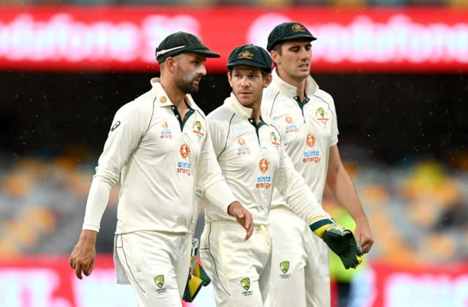 Tim Paine, Nathan Lyon and Pat Cummins leave the field as rain forces an early end to play on Day 4