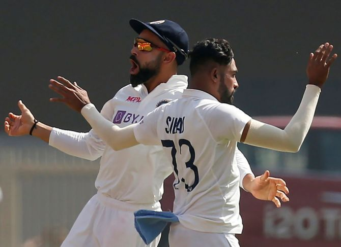 Virat Kohli and Mohammed Siraj celebrate the wicket of England's Joe Root on Day 1 of the 4th Test at Narendra Modi Stadium in Ahmedabad on Thursday