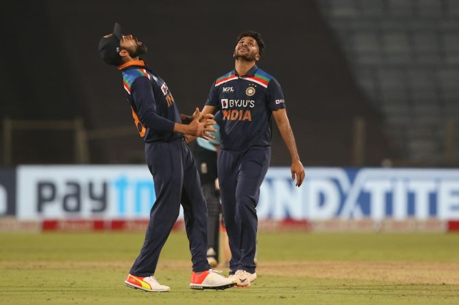 Virat Kohli and Shardul Thakur celebrate the wicket of England's Liam Livingstone the third One-Day International against England, in Pune, on Sunday.