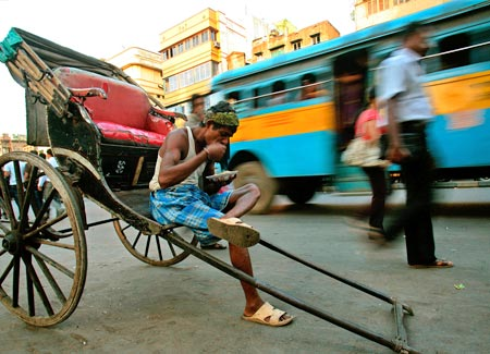 A rickshaw puller eats beside a busy road in Kolkata.