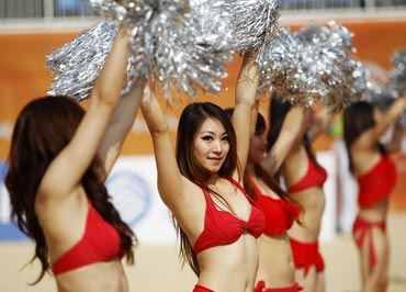 Cheerleaders perform a routine during the quarter-finals of the beach volleyball event at the 16th Asian Games in Guangzhou