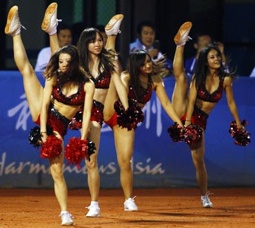 Cheerleaders perform a routine during the men's baseball final at the 16th Asian Games in Guangzhou