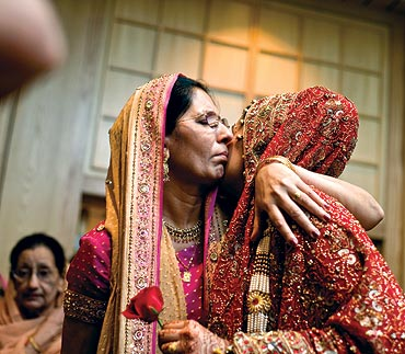 A bride hugs her mother after the wedding ceremony in Kuala Lumpur
