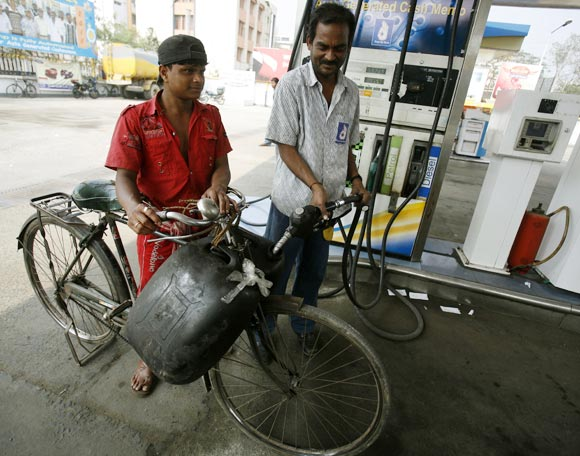 A worker (R) fills plastic containers with petrol at a pump