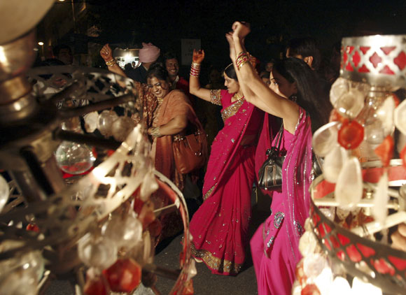 Indian women dance on the streets during a wedding in New Delhi