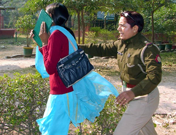 An Indian policewoman catches a young girl outside a park in Meerut where television channels filmed police officers repeatedly slapping, punching and pulling the hair of young women on a date in the Meerut park
