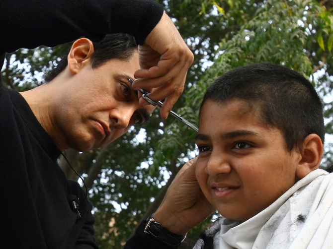 It is a myth that frequent haircuts make the hair grow faster. Seen here is Aamir Khan giving a haircut to a fan as part of a move promotion tour