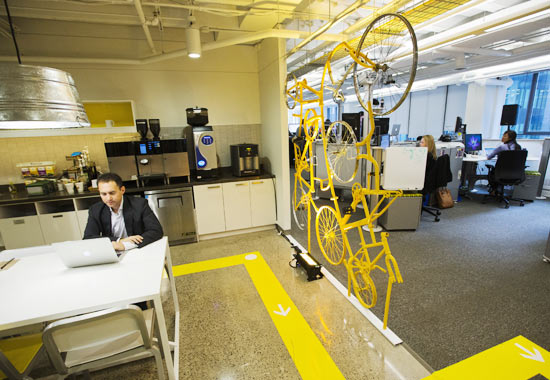 A Google employee works in the kitchen beside a structure made of recycled bicycles at the new Google office in Toronto