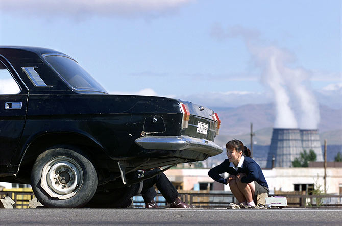 A Mongolian woman squats next to her broken down car near a power plant in Ulan Bator