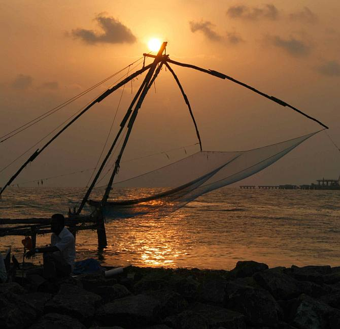 The sun sets over the Arabian Sea at Kochi even as the fishing nets sway in the wind
