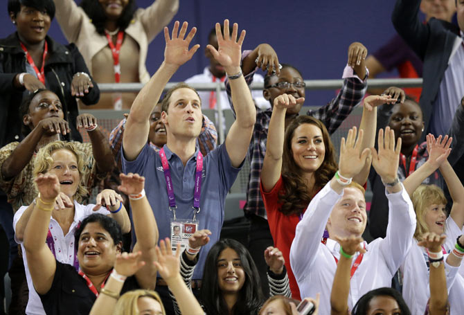 William and Kate participate in the Mexican Wave as they watch qualifying races during the London 2012 Paralympic Games.